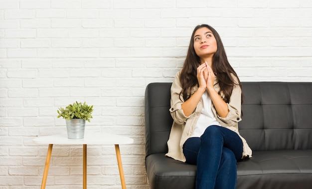 Młoda arabska kobieta siedzi na kanapie, tworząc plan, tworząc pomysł.