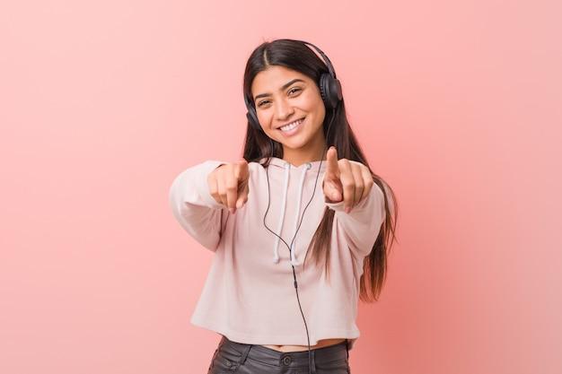 Młoda arabska kobieta słucha muzyki rozochoconych uśmiechów wskazuje przód.