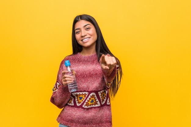 Młoda arabska kobieta trzyma bidonu rozochoconych uśmiechy wskazuje przód.