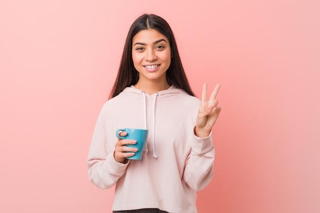 Młoda arabska kobieta trzyma filiżankę pokazuje numer dwa z palcami.