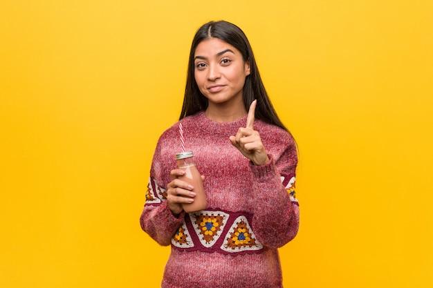 Młoda arabska kobieta trzyma smoothie pokazuje liczbę jeden z palcem.