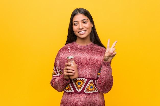 Młoda arabska kobieta trzyma smoothie pokazuje numer dwa z palcami.