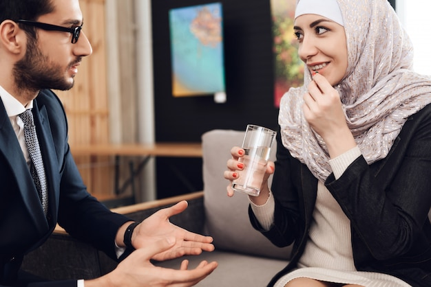 Młoda arabska kobieta w hidżabie bierze pigułkę.