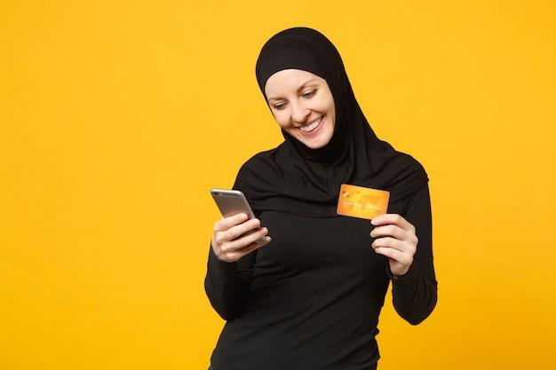 Młoda arabska muzułmanka w hidżab czarne ubrania trzymać w ręku telefon komórkowy, karta kredytowa na białym tle na żółtą ścianę portret. koncepcja życia religijnego ludzi.