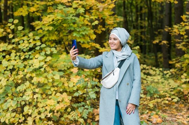 Młoda arabska muzułmanka w ubraniach hidżab robi selfie na telefonie komórkowym w parku ludzi