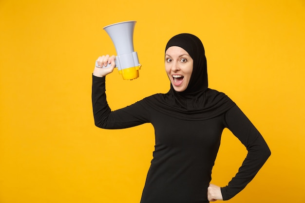 Młoda arabska muzułmańska kobieta w hidżab czarne ubrania trzyma w ręku bullhorn adres publiczny megafon na białym tle na portret żółtej ściany. koncepcja życia religijnego ludzi.