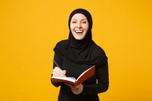 Młoda arabska muzułmańska kobieta w hidżabie czarne ubrania trzymaj notatnik, pisanie, przygotuj się do egzaminu na białym tle na portret żółtej ściany. koncepcja życia religijnego ludzi. .