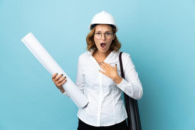 Młoda architekt gruzińska kobieta w kasku i trzymająca plany nad izolowaną ścianą zaskoczona i zszokowana, patrząc w prawo