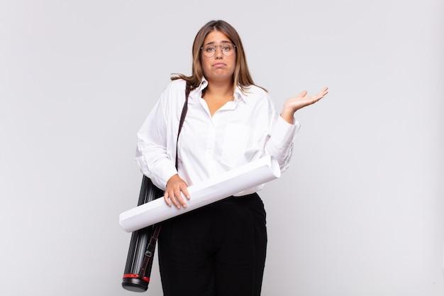 Młoda architekt kobieta czuje się zakłopotana i zdezorientowana, wątpi, waży lub wybiera różne opcje ze śmiesznym wyrazem twarzy