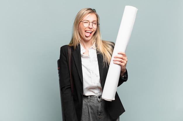 Młoda architekt kobieta o pogodnym, beztroskim, buntowniczym nastawieniu, żartująca i wystawiająca język, dobrze się bawiąca