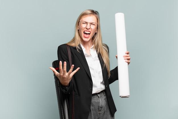 Młoda architekt, kobieta wyglądająca na złą, zirytowaną i sfrustrowaną, krzycząc wtf lub co jest z tobą nie tak