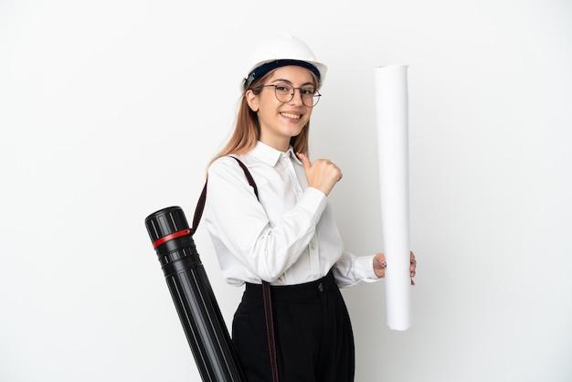 Młoda architekt kobieta z hełmem i trzymająca plany na białym tle