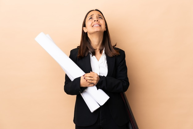 Młoda architekt kobiety mienia projekty nad odosobnionym tłem utrzymuje palmy wpólnie. osoba prosi o coś