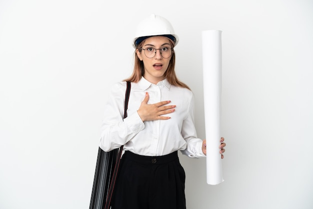 Młoda architekta kobieta z kaskiem i trzymając plany na białym tle