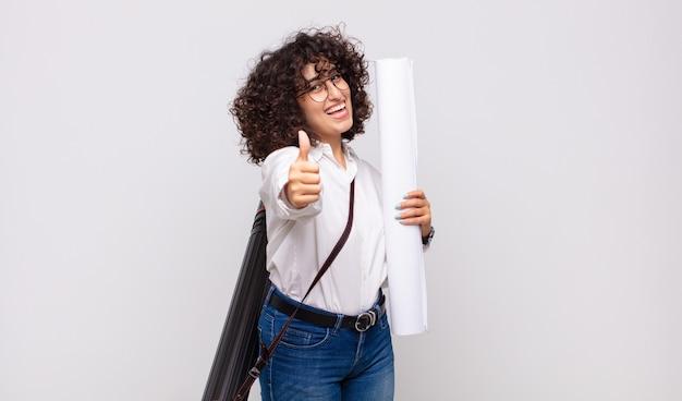 Młoda architektka czuje się dumna, beztroska, pewna siebie i szczęśliwa, uśmiechnięta pozytywnie z kciukami do góry
