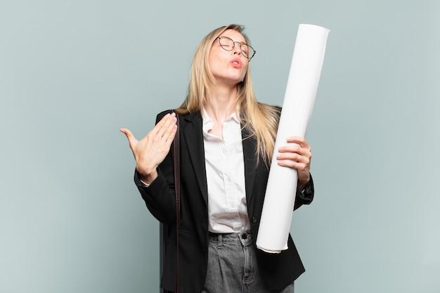 Młoda architektka czuje się zestresowana, niespokojna, zmęczona i sfrustrowana, ciągnie za koszulkę, wygląda na sfrustrowaną problemem