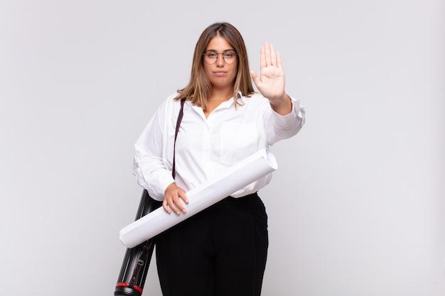 Młoda architektka kobieta wygląda poważnie, surowo, niezadowolona i zła, pokazując otwartą dłoń wykonującą gest stopu