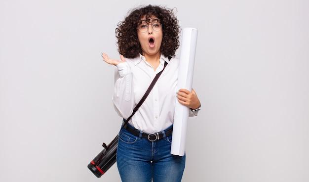 Młoda architektka wyglądająca na zaskoczoną i zszokowaną, z opuszczoną szczęką, trzymając przedmiot z otwartą ręką na boku
