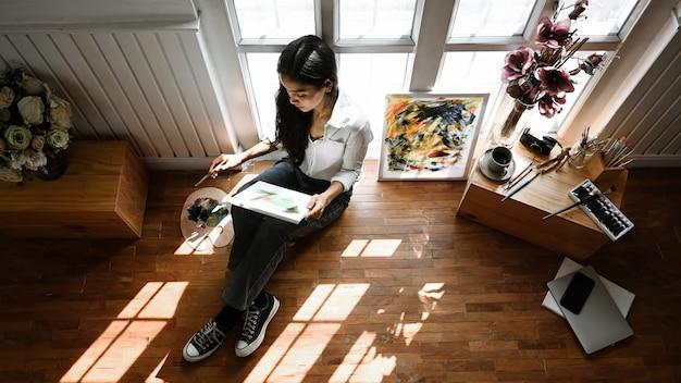 Młoda artysta dziewczyna siedzi i opiera się na oknach, patrząc koncentrując się na rysunku płótna.