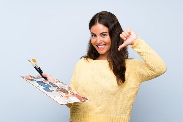 Młoda artysta kobieta nad odosobnioną błękit ścianą dumną i samozadowoloną
