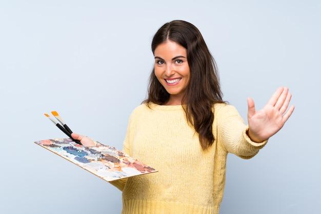 Młoda artysta kobieta nad odosobnioną błękit ścianą salutuje z ręką z szczęśliwym wyrażeniem