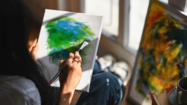 Młoda artysta kobieta rysuje obraz olejny podczas gdy siedzący przy drewnianą podłoga.