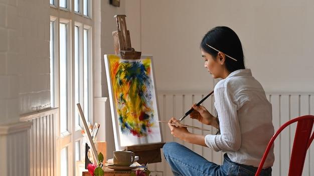 Młoda artysta kobieta rysuje wodnego kolor przy studiiem.
