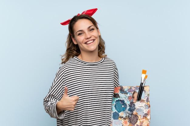 Młoda artysta kobieta trzyma paletę na pojedyncze niebieskie ściany z kciuki do góry, ponieważ stało się coś dobrego