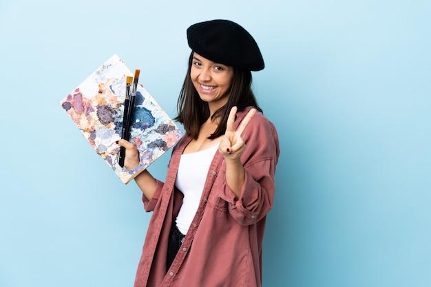 Młoda artysta kobieta trzyma paletę nad błękit ścianą uśmiecha się zwycięstwo znaka i pokazuje.