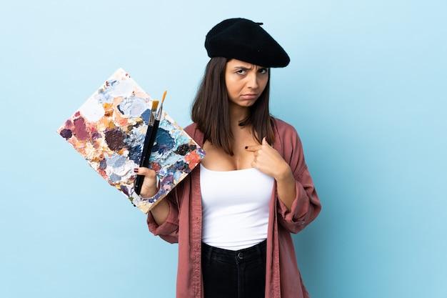 Młoda artysta kobieta trzyma paletę nad błękit ścianą wskazuje ona sama.