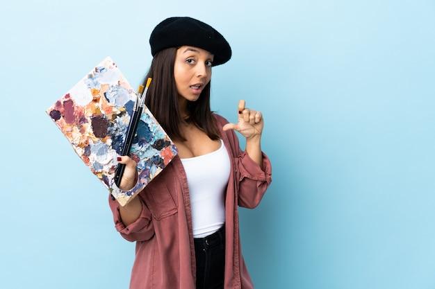 Młoda artysta kobieta trzyma paletę nad odosobnioną błękit ścianą dumną i zadowoloną z siebie