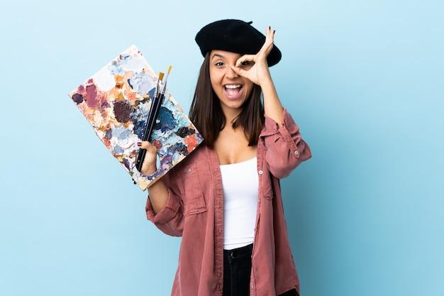 Młoda artysta kobieta trzyma paletę nad odosobnioną błękit ścianą pokazuje ok znaka z palcami