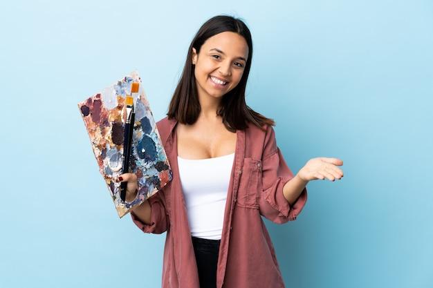 Młoda artysta kobieta trzyma paletę nad odosobnioną błękit ścianą przedstawia i zaprasza przychodzić z ręką
