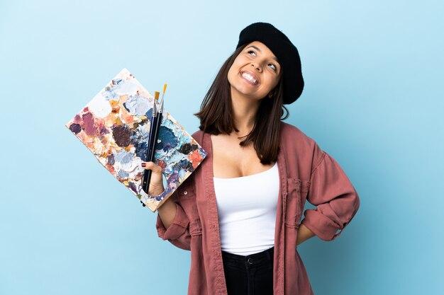Młoda artysta kobieta trzyma paletę nad odosobnioną błękit ścianą przyglądającą up podczas gdy ono uśmiecha się
