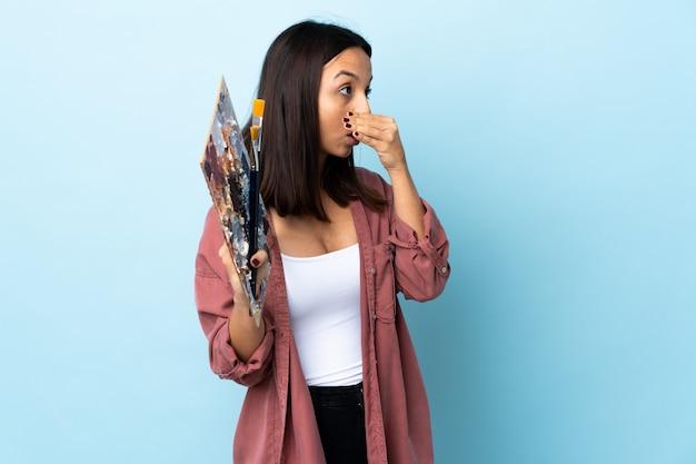 Młoda artysta kobieta trzyma paletę nad odosobnioną błękit ścianą robi niespodzianka gestowi podczas gdy patrzejący strona