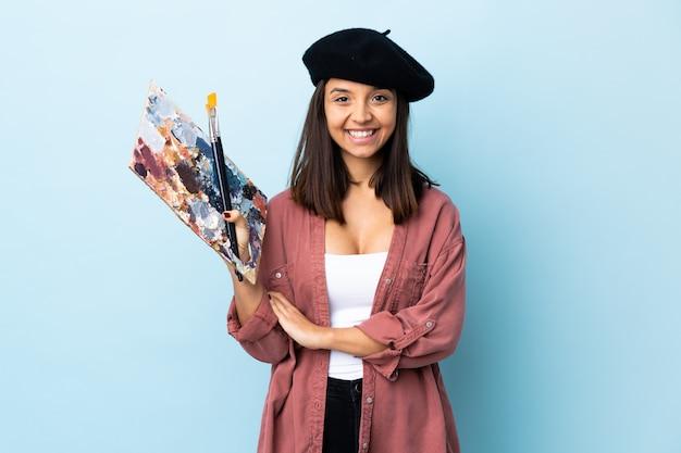 Młoda artysta kobieta trzyma paletę nad odosobnioną błękit ścianą utrzymuje ręki krzyżować w frontowej pozyci