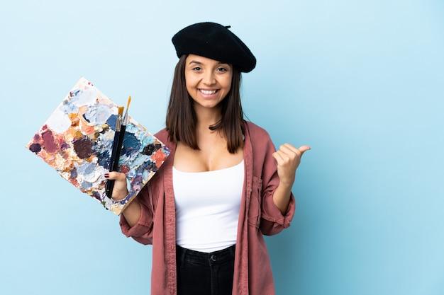 Młoda artysta kobieta trzyma paletę nad odosobnioną błękit ścianą wskazuje z boku przedstawiać produkt
