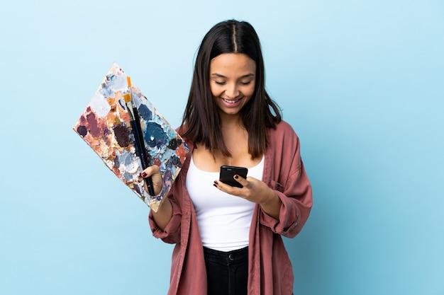 Młoda artysta kobieta trzyma paletę nad odosobnioną błękit ścianą wysyła wiadomość z wiszącą ozdobą