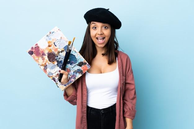 Młoda artysta kobieta trzyma paletę nad odosobnioną błękit ścianą z niespodzianka wyrazem twarzy