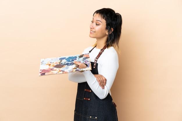 Młoda artysta kobieta trzyma paletę nad odosobniony patrzeć strona