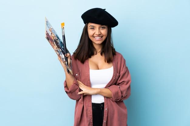 Młoda artysta kobieta trzyma paletę nad odosobnionym błękit ściany śmiać się
