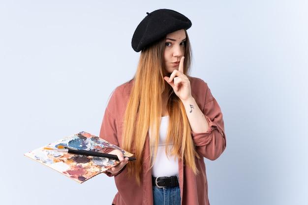 Młoda artysta kobieta trzyma paletę odizolowywająca na błękit ścianie robi cisza gestowi