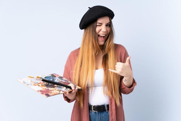 Młoda artysta kobieta trzyma paletę odizolowywająca na błękit ścianie robi telefonu gestowi