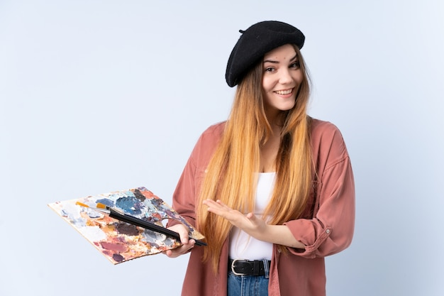 Młoda artysta kobieta trzyma paletę odizolowywającą na błękit ścianie rozciąga ręki z boku dla zapraszać przyjeżdżać