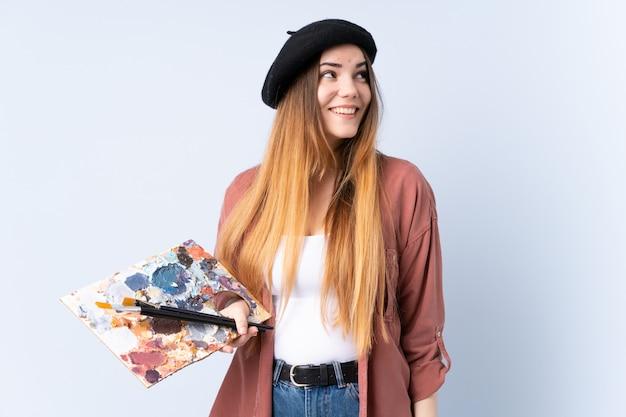 Młoda artysta kobieta trzyma paletę odizolowywająca na błękit ścianie śmia się i przygląda up