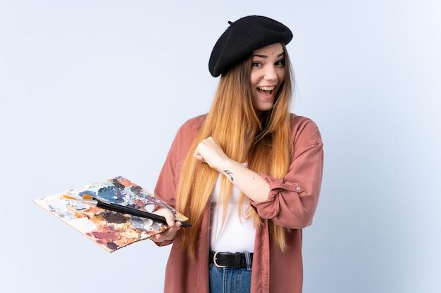 Młoda artysta kobieta trzyma paletę odizolowywająca na błękit ścianie świętuje zwycięstwo