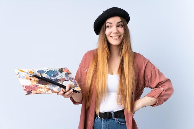 Młoda artysta kobieta trzyma paletę odizolowywającą na błękit ścianie trzyma copyspace imaginacyjnego na palmie