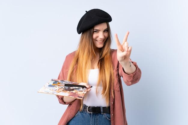 Młoda artysta kobieta trzyma paletę odizolowywająca na błękit ścianie uśmiecha się zwycięstwo znaka i pokazuje