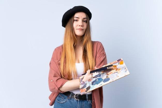 Młoda artysta kobieta trzyma paletę odizolowywająca na błękit ścianie utrzymuje ręki krzyżować