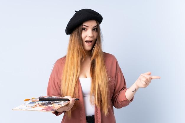 Młoda artysta kobieta trzyma paletę odizolowywającą na błękit ścianie zaskakuje i wskazuje palec z boku